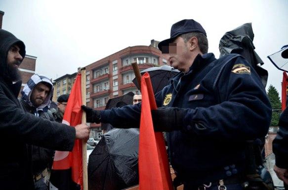 Un policía examina las banderas de los manifestantes. Imagen de Pablo Gómez