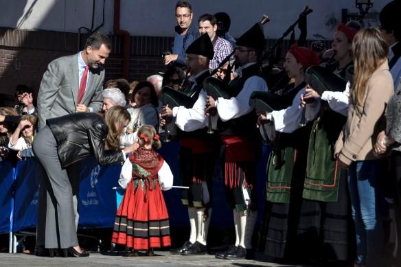 Los Príncipes saludan a una niña que acompaña a la banda de gaitas con el traje tradicional. Imagen de Pablo Gómez